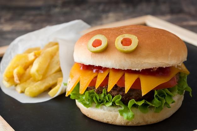 Halloween-burgermonster mit pommes-frites auf hölzerner tabelle