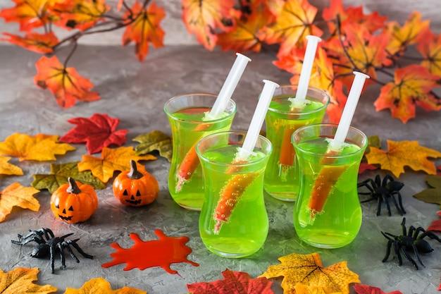 Halloween cocktails. spritzen mit blut in gläsern mit grüner limonade, spinnen
