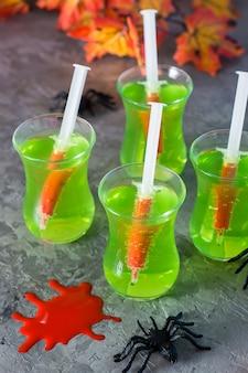 Halloween cocktails. spritzen mit blut in gläsern mit grüner limonade und spinne auf dem tisch.