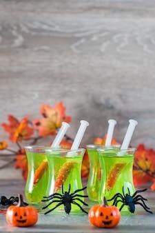 Halloween cocktails. spritzen mit blut in gläsern mit grüner limonade und spinnen auf dem tisch.