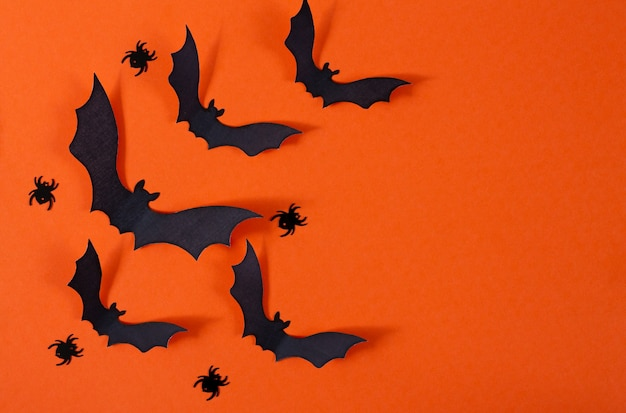 Halloween-dekor mit spinnen und schwarzen papierfledermäusen, die über orange hintergrund fliegen
