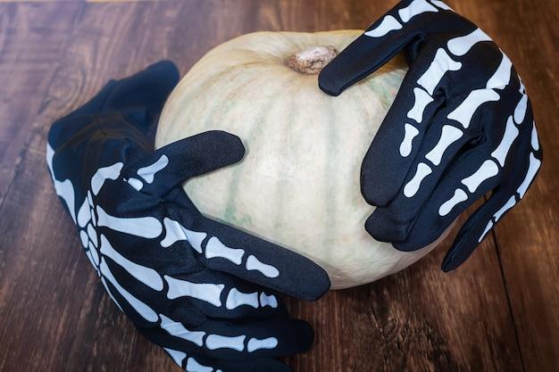 Halloween-dekoration auf einem hölzernen hintergrund. skeletthandschuhe halten einen kürbis