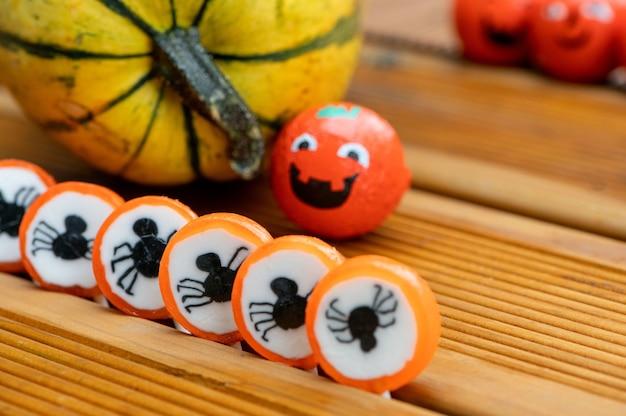 Halloween dekoration hintergrund mit kürbissen und süßigkeiten bonbons auf der heimischen holzterrasse