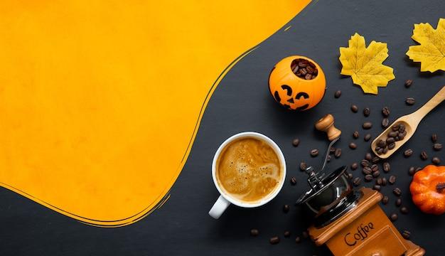 Halloween-dekoration mit heißem kaffee und bohnen auf dunklem hintergrund. flach liegen. kopieren sie platz für text.