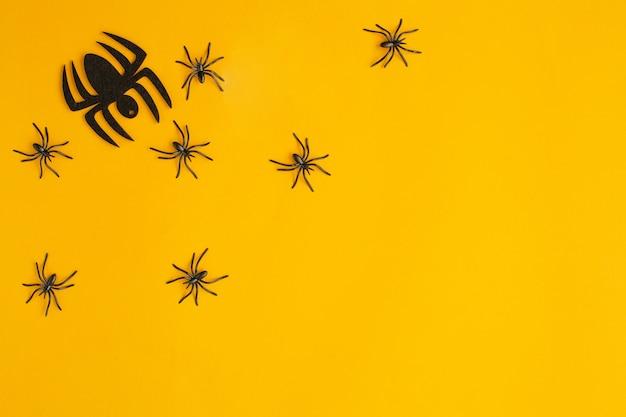 Halloween-dekorationen mit spinnen auf orange hintergrund. draufsicht, kopierraum, flache lage.