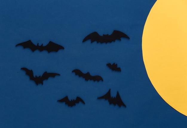 Halloween, dekorationen und gruseliges konzept. schwarze fledermäuse fliegen über blaue dunkle nacht mit gelbem mond