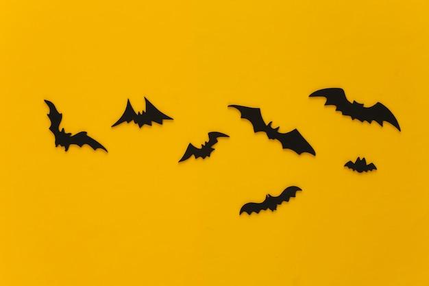 Halloween, dekorationen und gruseliges konzept. schwarze fledermäuse fliegen über gelb