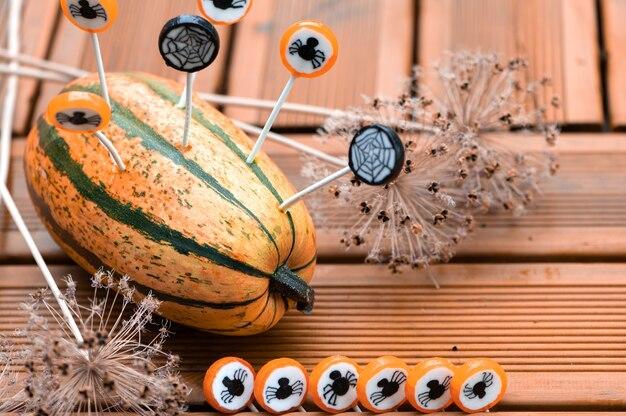 Halloween-dekorationshintergrund mit kürbis und runden bonbons, auf denen schwarze käfer und spinnweben