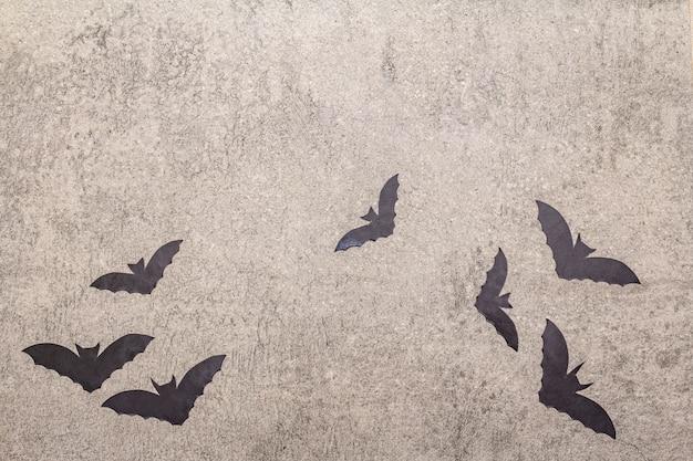 Halloween-dekorationskonzept - schwarze schläger auf grauem steinbetonhintergrund