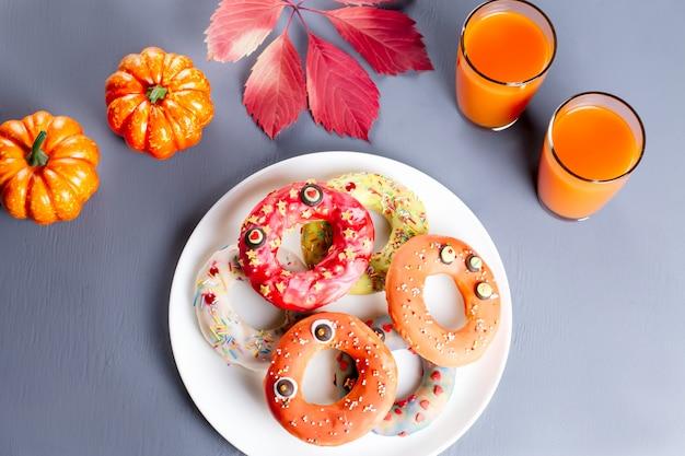 Halloween donuts mit kürbissaft und herbstlaub.