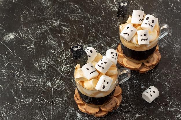 Halloween-drink - gruselige gesichter (monster) von marshmallows in einer tasse kaffee