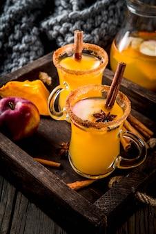 Halloween, erntedankfest. traditionelle herbst-, wintergetränke und cocktails. würzige heiße kürbissangria, mit apfel, zimt, anis. im tablett rustikaler holztisch, glasbecher. tiefenschärfe textfreiraum