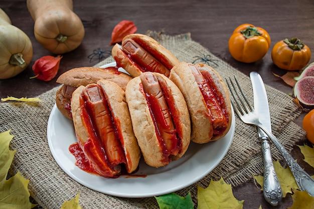 Halloween essen. halloween-hotdog. blutige finger von würstchen in brötchen mit ketchup. gruseliges essen.
