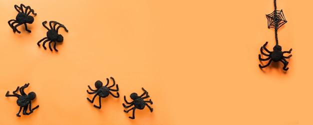 Halloween-fahne mit schwarzen spinnen, web auf orange. flachgelegt, draufsicht. copyspace.