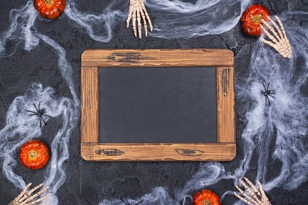 Halloween-feiertag mit skeletthänden, kürbissen, spinnen und spinnennetz auf schwarz
