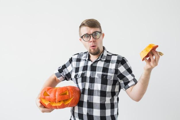 Halloween-, feiertags-, herbst- und menschenkonzept - glücklicher mann, der einen kürbislaterne hält.