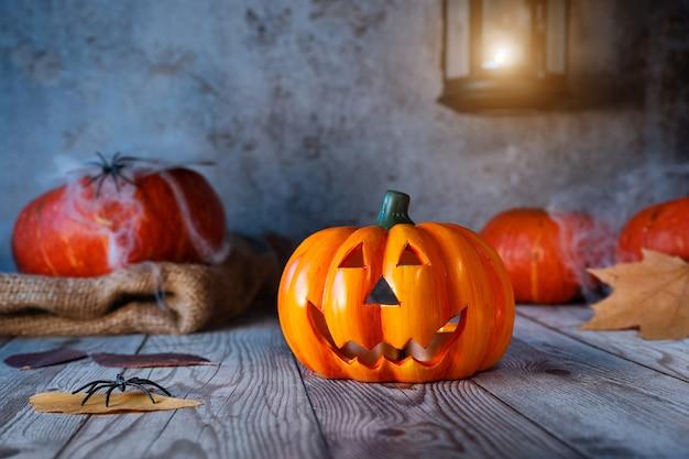 Halloween-feiertagshintergrund mit kürbislaterne, kürbissen, spinnennetz und beleuchteter laterne auf rustikalem hintergrund. nachtszene.