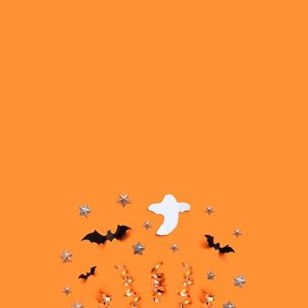Halloween-feiertagshintergrund mit schlägern, geist, sternen und dekorationen auf einem orange brett.