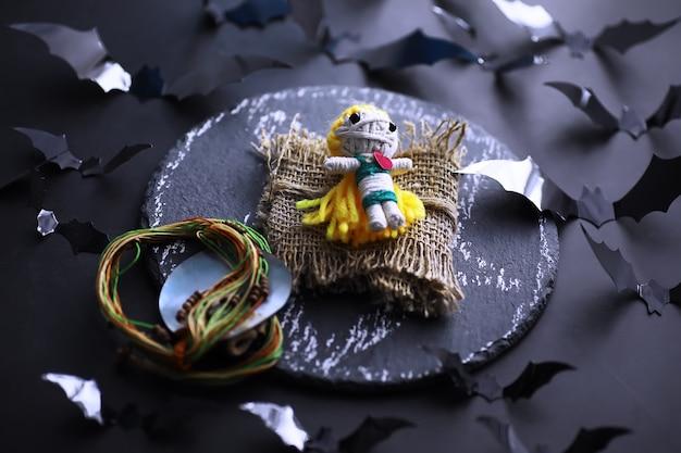 Halloween-feiertagskonzept. alter steintisch in form von fledermäusen. halloween-papierdekorationen auf dunklem hintergrund. mond spielzeug.
