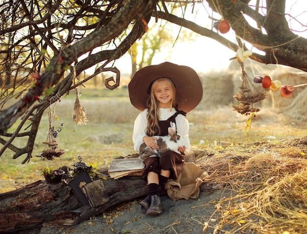 Halloween. fröhliche hexe mit zauberstab und buch zaubert und lacht. kleines mädchen im hexenkostüm