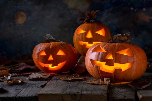 Halloween. furchtsamer nächtlicher himmel mit vollmond. eine gruppe von drei kürbisen und von gefallenen trockenen blättern auf holztisch. nahansicht.