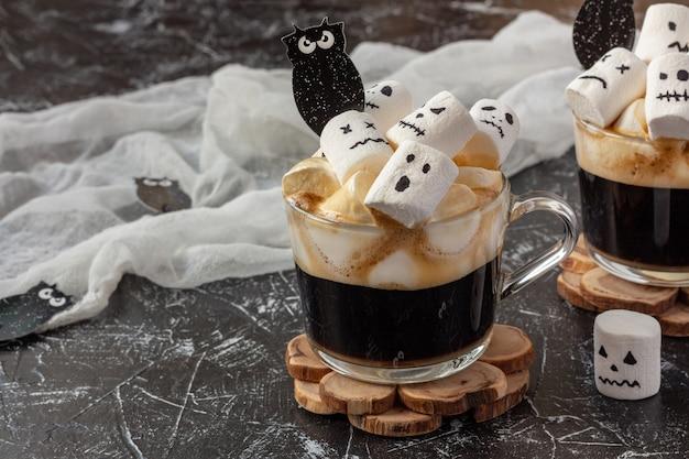 Halloween-getränk - zwei tassen kaffee mit marshmallow (gruselige gesichter, monster) auf dunklem tisch