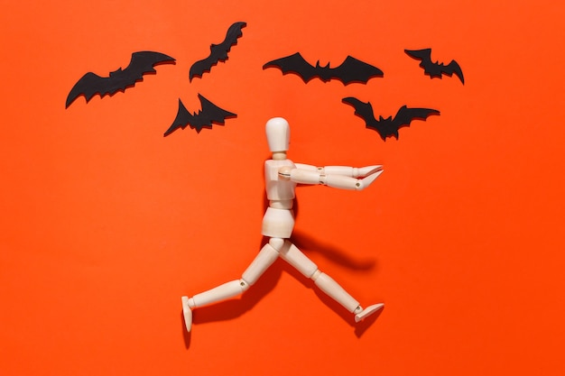 Halloween-gruseliges konzept. holzpuppe läuft auf leuchtendem orange mit fliegenden fledermäusen davon