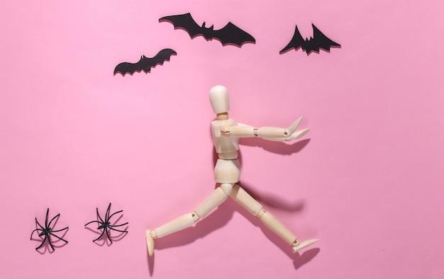 Halloween-gruseliges konzept. holzpuppe läuft auf rosa leuchtend mit fliegenden fledermäusen, spinnen davon spider