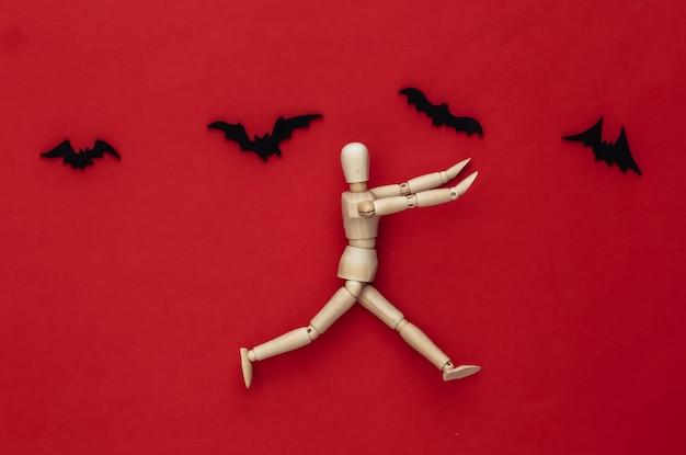 Halloween-gruseliges konzept. holzpuppe läuft auf rot mit fliegenden fledermäusen davon