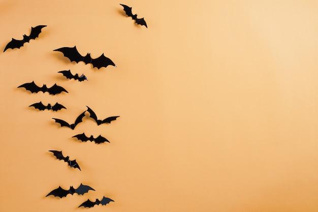 Halloween-handwerk, schwarze papierschläger, die über orange hintergrund fliegen