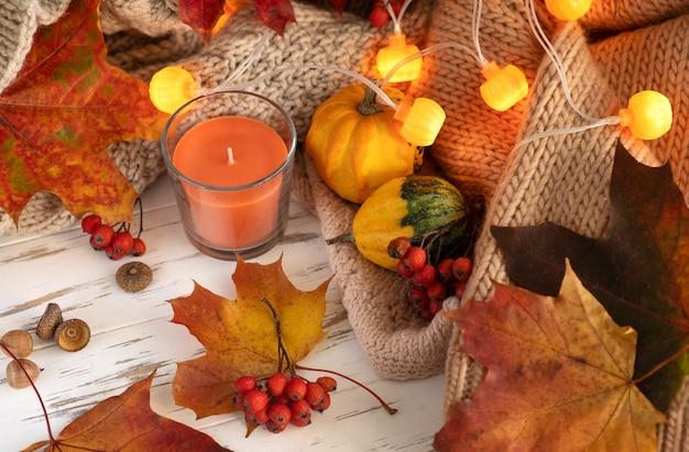 Halloween. herbstzusammensetzung. gefallene helle blätter, aromakerze, zapfen, glühbirnen in form eines kürbises auf einem hölzernen hintergrund. nahaufnahme.