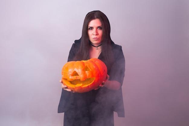 Halloween-hexe, die einen orange kürbis jack o lantern mit rauch hält.