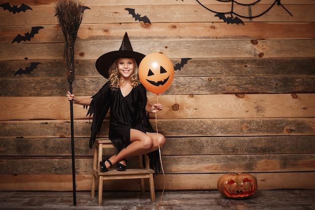 Halloween-hexe-konzept - ganzaufnahme eines kleinen kaukasischen hexenkindes, das mit magischem besen über fledermaus- und spinnennetzhintergrund posiert.