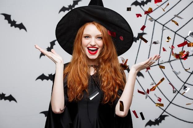 Halloween-hexe-konzept - glückliche elegante hexe, die konfetti wirft, um halloween-party über fledermaus- und spinnenwand zu feiern.