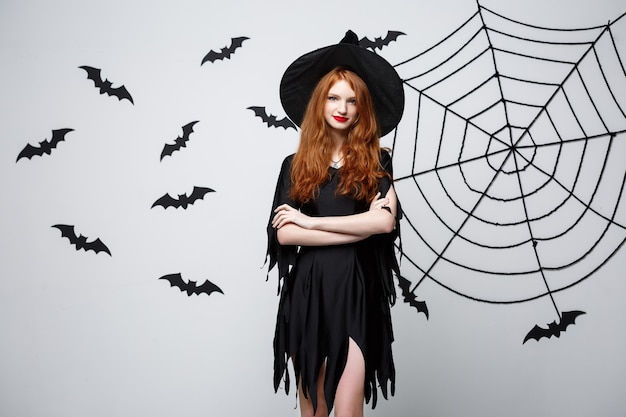 Halloween-hexe-konzept glückliche halloween-hexe, die über dunkelgrauer wand mit fledermaus und spinnennetz posiert
