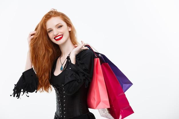 Halloween-hexe-konzept glückliche halloween-hexe lächelt und hält bunte einkaufstüten auf weißer wand