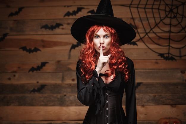 Halloween-hexe-konzept - glückliches halloween-rotes haar hexe, die ruhegeste mit dem finger auf ihren lippen über altem hölzernem studiohintergrund tut.