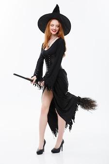 Halloween-hexe-konzept in voller länge glückliche elegante hexe mit besenstiel zum feiern von halloween-party über weißer wand