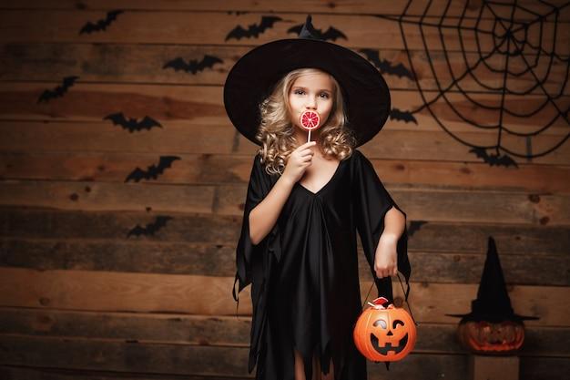Halloween-hexe-konzept - kleine hexe kind mit halloween süß und süßigkeiten mit fröhlichen lächeln. über fledermaus und spinnennetz hintergrund.