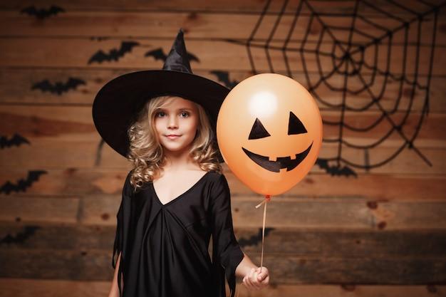 Halloween-hexe-konzept - kleines kaukasisches hexenkind genießt mit halloween-ballon. über fledermaus- und spinnennetzhintergrund.