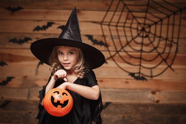 Halloween-hexe-konzept - kleines kaukasisches hexenkind genießt mit halloween-süßigkeiten-kürbisglas. über fledermaus- und spinnennetzhintergrund.