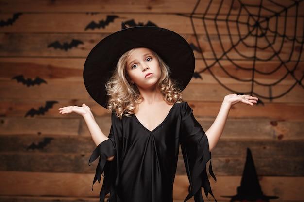 Halloween-hexe-konzept - nahaufnahme des kleinen kaukasischen hexenkindes, das händchen beiseite hält.