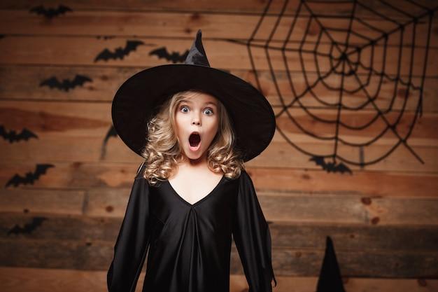 Halloween-hexe-konzept - nahaufnahme des kleinen kaukasischen hexenkindes, das schockierendes gesicht mit fledermaus und spinnennetz auf hölzernem studiohintergrund aufwirft.
