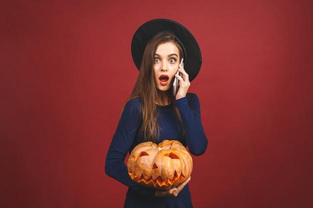 Halloween-hexe mit einem geschnitzten kürbis - lokalisiert auf rotem hintergrund. emotionale junge frau im halloween-kostüm. telefon benutzen.