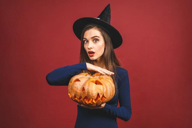Halloween-hexe mit einem geschnitzten kürbis - lokalisiert auf rotem hintergrund. emotionale junge frau im halloween-kostüm.