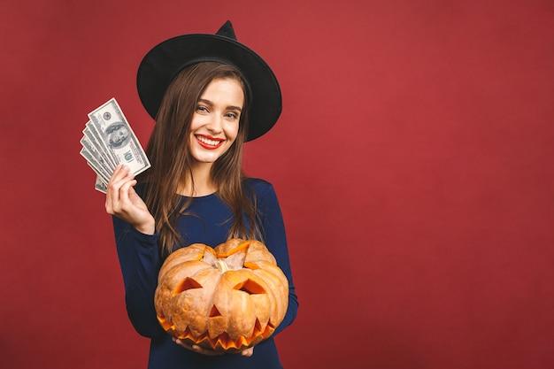Halloween-hexe mit einem geschnitzten kürbis und geld - lokalisiert auf rotem hintergrund. emotionale junge frau im halloween-kostüm.