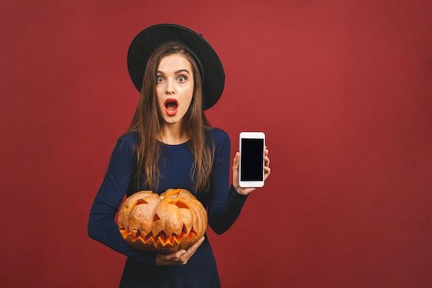 Halloween-hexe mit einem geschnitzten kürbis und handy-bildschirm - lokalisiert auf rotem hintergrund. emotionale junge frau im halloween-kostüm.