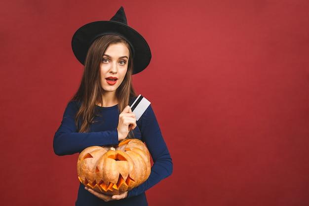 Halloween-hexe mit einem geschnitzten kürbis und kreditkarte - lokalisiert auf rotem hintergrund. emotionale junge frau im halloween-kostüm.