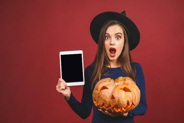 Halloween-hexe mit einem geschnitzten kürbis- und tablettbildschirm - lokalisiert auf rotem hintergrund. emotionale junge frau im halloween-kostüm.