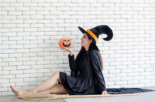 Halloween-hexe mit einem magischen kürbis, schöne junge frau im hexenhut und -kostüm